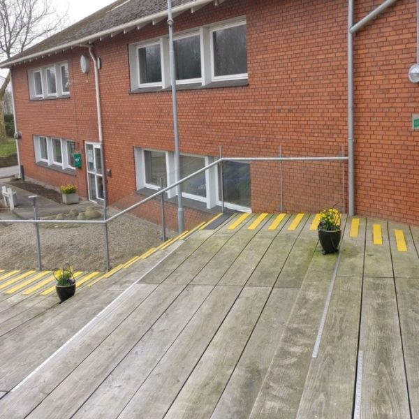 Deck strips in yellow mounted on wood.
