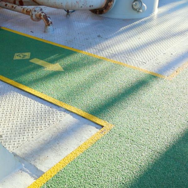 Skridsikker plade med piktogram i grøn på riggen.