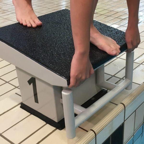Skridsikker plade i sort i svømmehal.