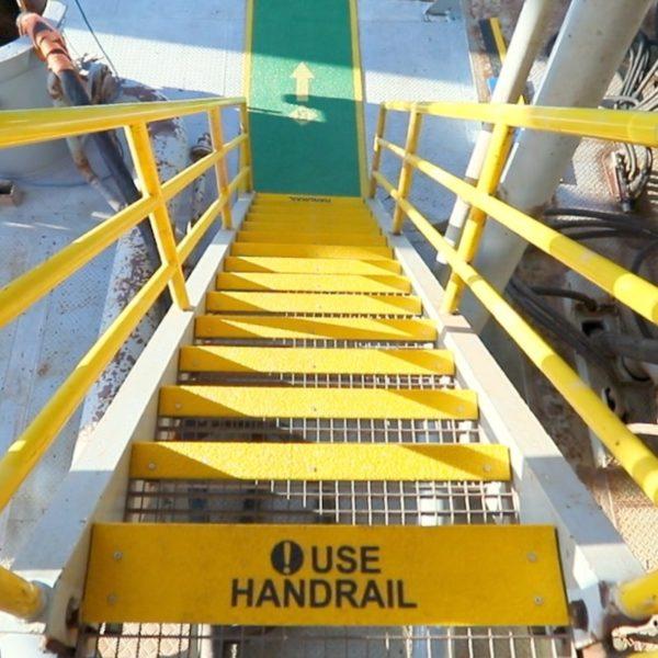 Stair nosing in yellow mounted on steel gratings.