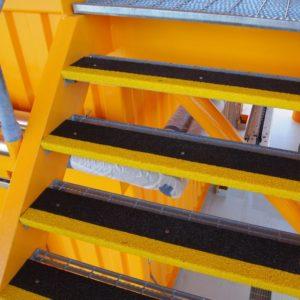 Anti-slip step covers mounted on steel gratings.