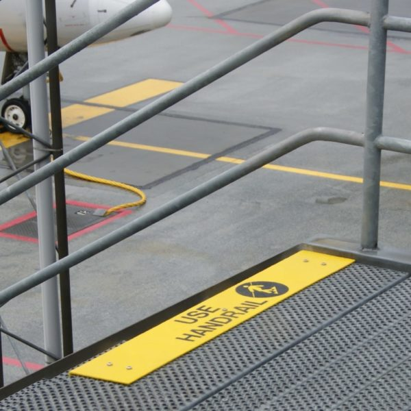 Trinsikring med nudging tekst og piktogram i gul ved lufthavn.