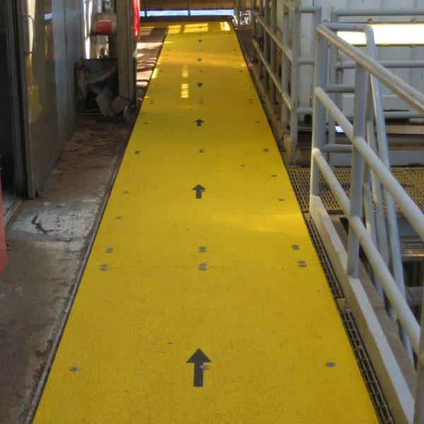 Anti-slip walkway covers mounted on steel gratings.