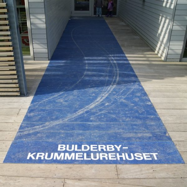 Walkway covers with text in blue on wood at kindergarten.
